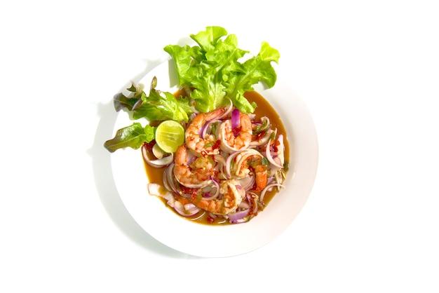 Pittige salade met garnalen en chilipasta. thais voedsel op schotel die op witte achtergrond wordt geïsoleerd