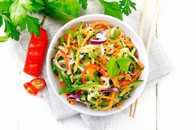 Pittige salade van komkommers, wortelen, chilipepers, paarse uien, koriander en zwarte sesam