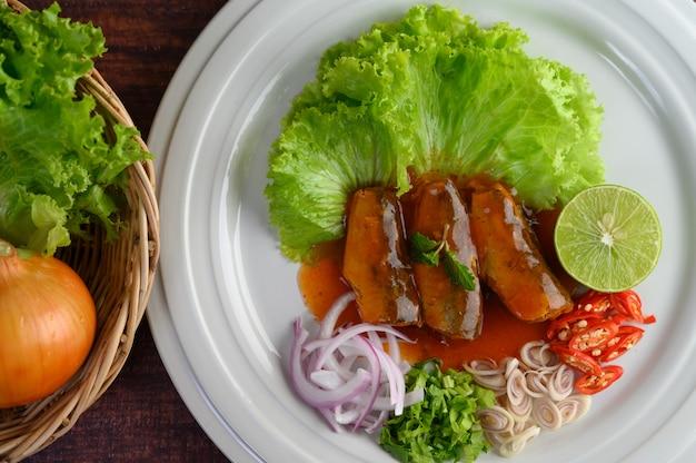 Pittige salade van sardine met tomatensaus in witte schotel