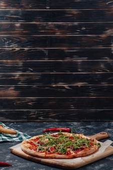 Pittige, smakelijke napolitaanse pizza aan boord met cherrytomaatjes en chili, vrije ruimte voor tekst