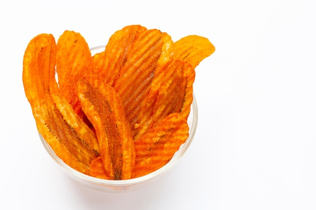 Pittige snack, banana slice chips paprika smaak in glazen kom op witte achtergrond.