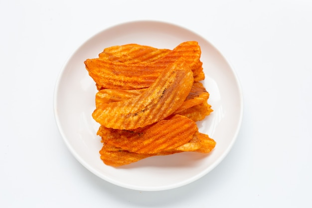 Pittige snack, banana slice chips paprika smaak in witte plaat op witte achtergrond.