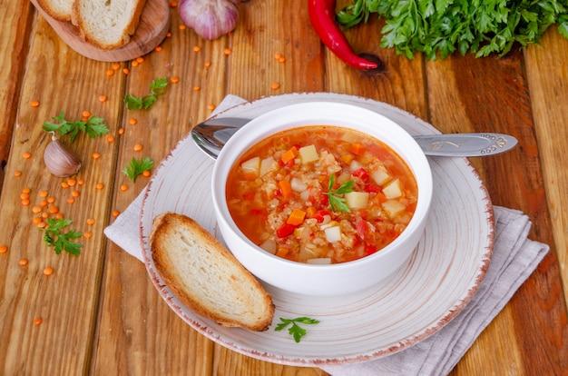Pittige soep met rode linzen, tomaten, prei, paprika, wortelen en aardappelen.
