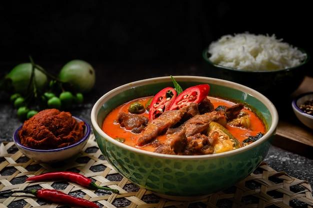 Pittige thaise curry met varkensvlees serveren met rijst en decoreren met plantaardige ingrediënten zoals chili en aubergine op rustieke achtergrond - thais eten