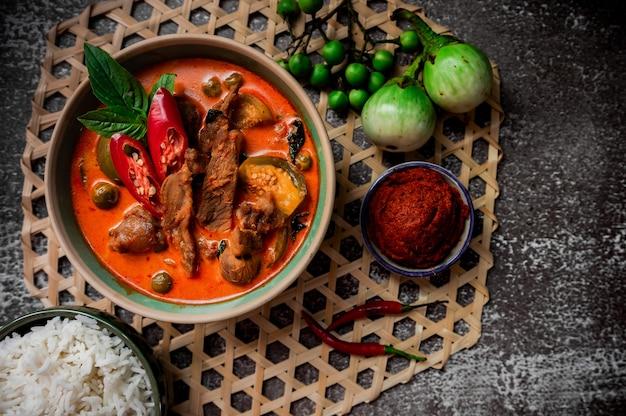 Pittige thaise curry met varkensvlees serveren met rijst en decoreren met plantaardige ingrediënten zoals chili en aubergine op rustieke achtergrond