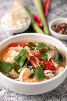 Pittige tom yam kung, tom yum zure soep met garnalen, garnalen, kokosmelk, citroengras en chilipeper in een kom