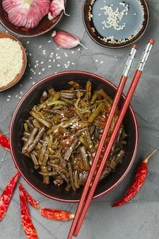Pittige varensalade met ui, knoflook, chilipeper, sojasaus, sesamzaad en specerijen, oosterse en aziatische gerechten, chinees
