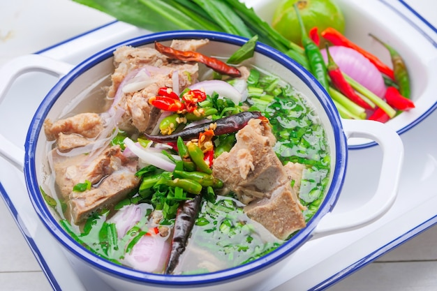Pittige varkensbotensoep in thaise stijl is een heldere varkensbotensoep met grote varkensbotjes, versierd met chili en thaise kruiden