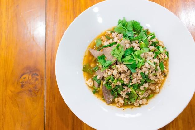 Pittige varkensgehaktsalade is een traditioneel gerecht uit het noordoosten van thailand. het bevat varkensgehakt