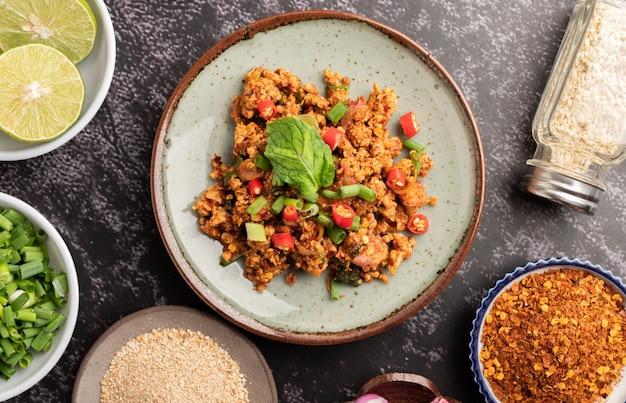 Pittige varkensgehaktsalade met chilivlokken, limoen, gehakte groene uien, chili en geroosterde rijst