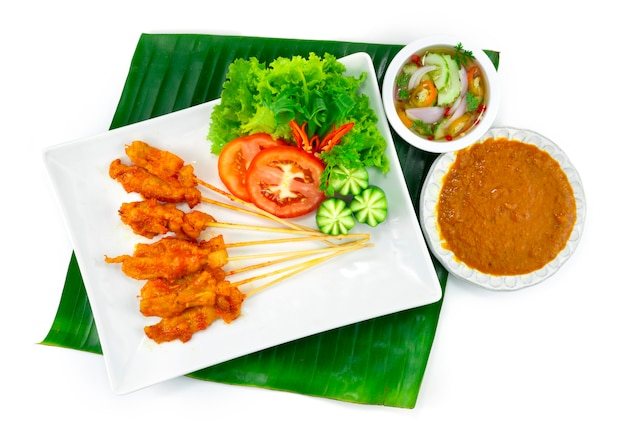 Pittige varkenssaté of pittig gegrild varkensvlees in spiesjes geserveerd dipsaus met chili pindasaus, zoetzure saus thaise voorgerecht schotel decoratie met snijwerk groenten bovenaanzicht