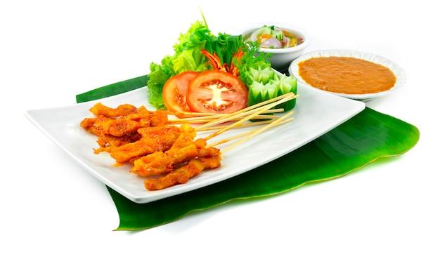 Pittige varkenssaté of pittig gegrild varkensvlees in spiesjes geserveerd dipsaus met chili pindasaus, zoetzure saus thaise voorgerecht schotel decoratie met snijwerk groenten zijaanzicht