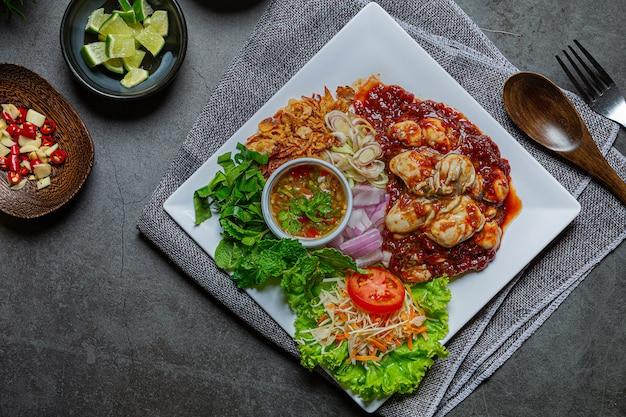 Pittige verse oestersalade en thaise voedselingrediënten.
