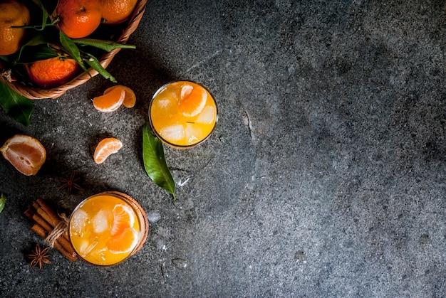 Pittige winter mandarijn cocktail met wodka, verse mandarijnen, kaneel en anijs, op donkere achtergrond, kopie ruimte bovenaanzicht