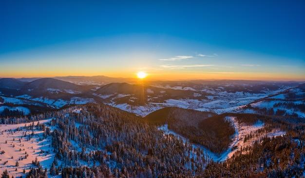 Pittoresk de winterpanorama van bergheuvels bedekt met sneeuw en sparren op een zonnige heldere dag met de zon en de blauwe hemel
