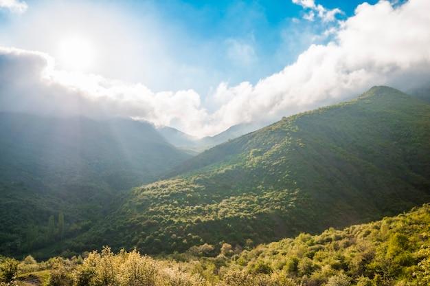 Pittoresk landschap, regenwolken, bergen bedekt met groene planten, landwegpassen tussen heuvels