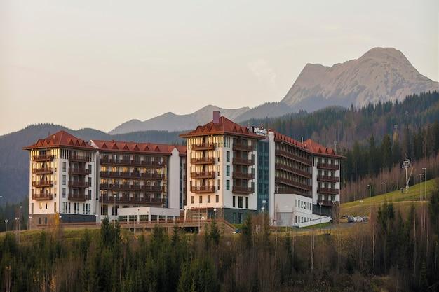 Pittoreske grote luxe hotelcomplex buitenkant, toeristische accommodatie met moderne architectuur op groene spar bergrug en heldere hemel. toerisme en recreatie.