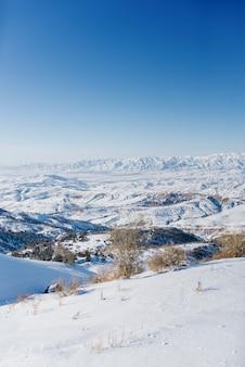 Pittoreske tien shan-gebergte in oezbekistan, bedekt met sneeuw, heldere winter zonnige dag