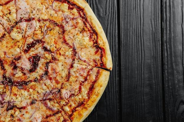 Pizza barbecuesaus met kip op zwarte houten achtergrond bovenaanzicht