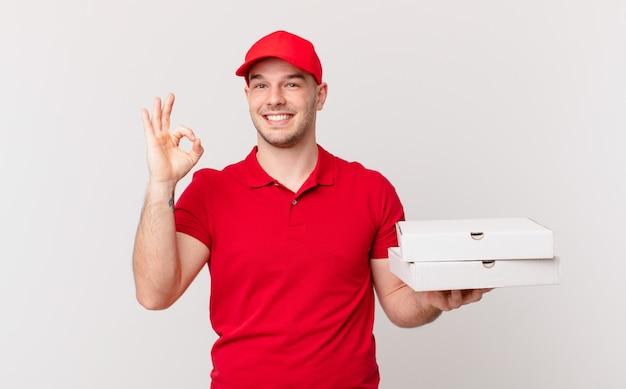 Pizza bezorger die zich gelukkig, ontspannen en tevreden voelt, goedkeuring toont met een goed gebaar, glimlachend