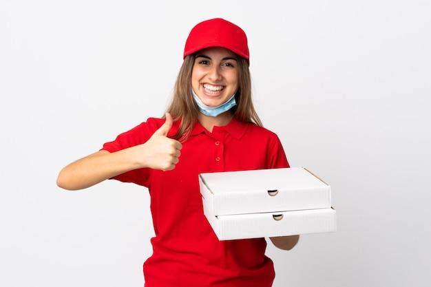 Pizza bezorger houdt een pizza vast en beschermt tegen het coronavirus met een masker op geïsoleerde witte muur met duimen omhoog omdat er iets goeds is gebeurd
