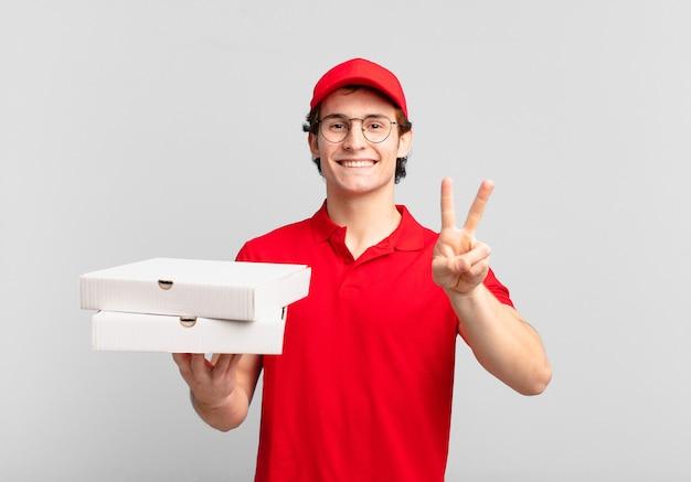 Pizza bezorger lacht en ziet er gelukkig, zorgeloos en positief uit, gebaart overwinning of vrede met één hand