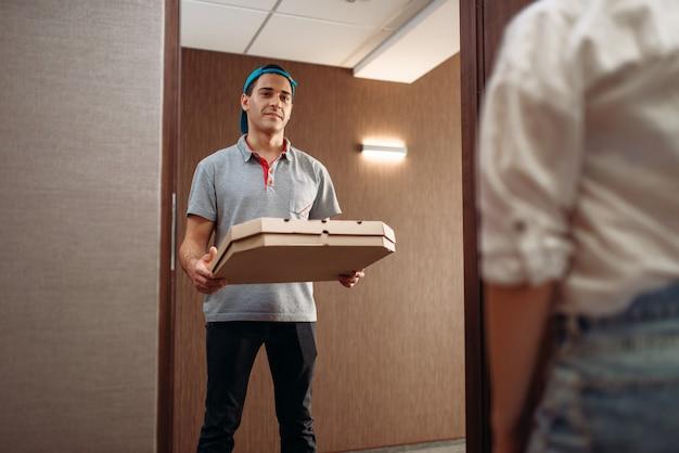 Pizza bezorger met kartonnen doos in handen voor de deur, service leveren. koerier van pizzeria en klant binnen