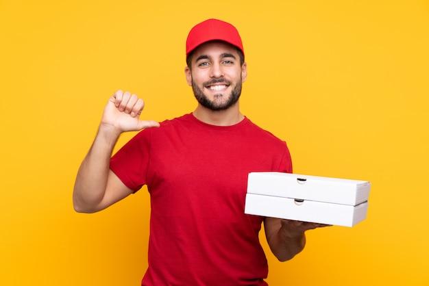 Pizza bezorger met werk uniform oppakken van pizzadozen over geïsoleerde gele trots en zelfvoldaan