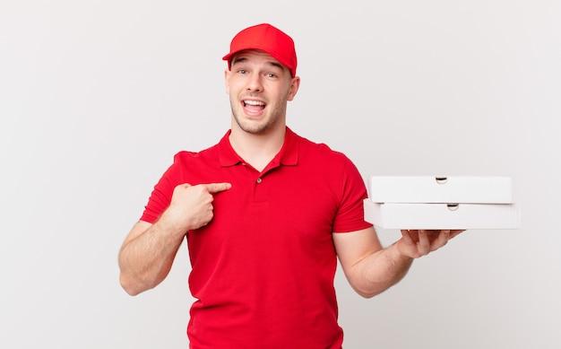 Pizza bezorger voelt zich blij, verrast en trots, wijzend naar zichzelf met een opgewonden, verbaasde blik