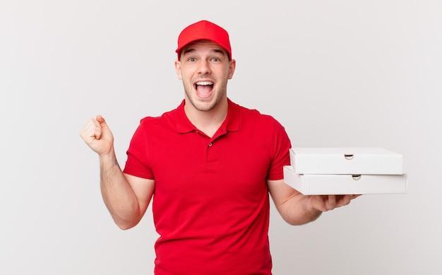 Pizza bezorger voelt zich geschokt, opgewonden en blij, lacht en viert succes en zegt wauw!