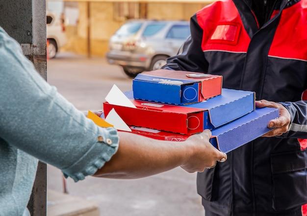 Pizza bezorging. een koerier die pizzadozen aan een persoon geeft.