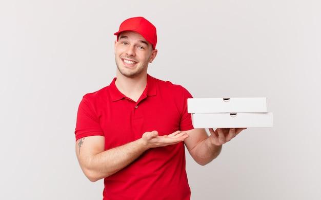 Pizza bezorgt een man die vrolijk lacht, zich gelukkig voelt en een concept in de kopieerruimte laat zien met de palm van de hand