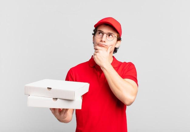 Pizza bezorgt jongen die denkt, zich twijfelachtig en verward voelt, met verschillende opties, zich afvragend welke beslissing hij moet nemen?