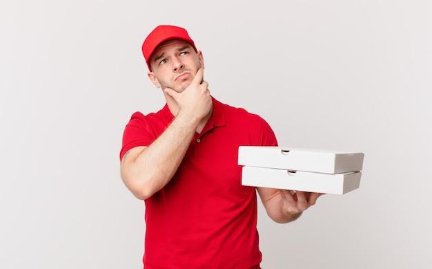 Pizza bezorgt man denken, zich twijfelachtig en verward voelen, met verschillende opties, zich afvragend welke beslissing hij moet nemen?