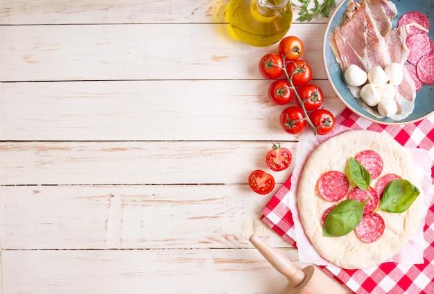 Pizza die achtergrond maakt. ingrediënten voor het maken van pizza.