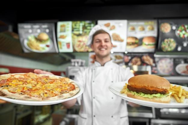 Pizza en haumburger met gratis aardappel in handen van mannelijke kok