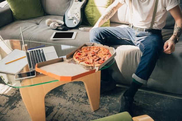 Pizza eten. man die thuis studeert tijdens online cursussen, slimme school. lessen of beroep krijgen terwijl je geïsoleerd bent, quarantaine tegen verspreiding van het coronavirus. met behulp van laptop, smartphone, koptelefoon.