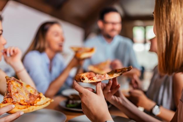Pizza eten met vrienden. detailopname.