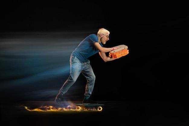 Pizza feest. snelle bezorgservice - bezorger op eenwieler rijden met bestelling in brand op donkere muur