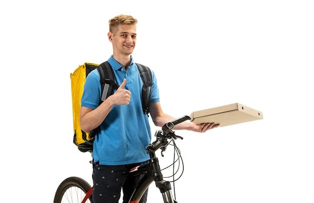 Pizza geven. bezorger met fiets geïsoleerd op een witte studio achtergrond. contactloze dienstverlening tijdens quarantaine. man levert voedsel tijdens isolatie. veiligheid. beroepsberoep. copyspace, flyer