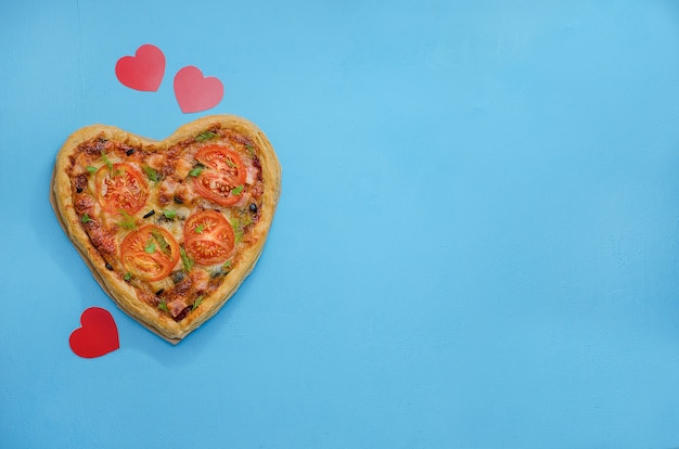 Pizza in de vorm van een hart op een blauwe tafel met rode harten. bestel pizza voor een romantisch diner op valentijnsdag. liefde.