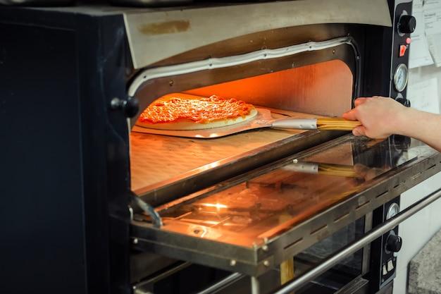 Pizza in een elektrische oven plaatsen