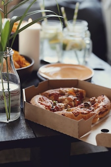 Pizza in een kartonnen doos en snacks