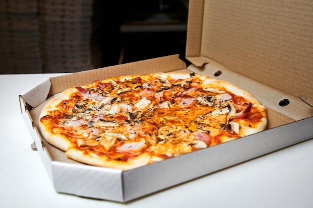 Pizza in een open doos klaargemaakt voor bezorging