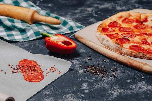 Pizza-ingrediënten op donkere betonnen ondergrond, napolitaanse pizza, koken concept