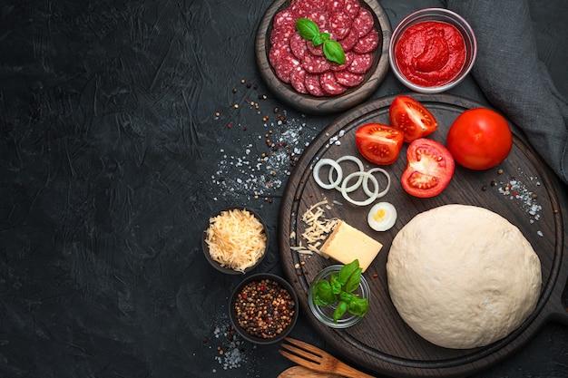 Pizza-ingrediënten op een zwarte achtergrond.