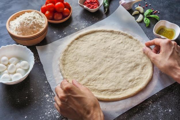 Pizza koken. het maken van deeg door vrouwelijke handen bij bakkerij. italiaanse pizza margarita maken.