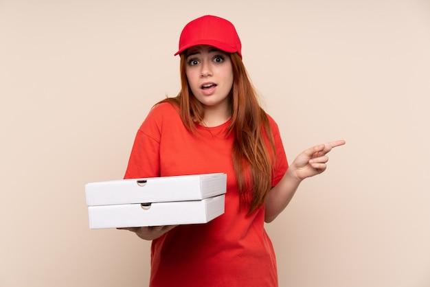 Pizza levering tiener meisje houdt van een pizza over geïsoleerde muur wijst naar de zijkanten met twijfels