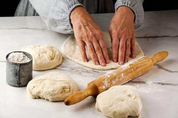 Pizza maken, vrouwenhand die met deeg en bloem werken