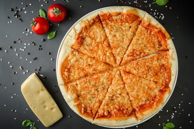 Pizza margarita en ingrediënten op een donkere achtergrond